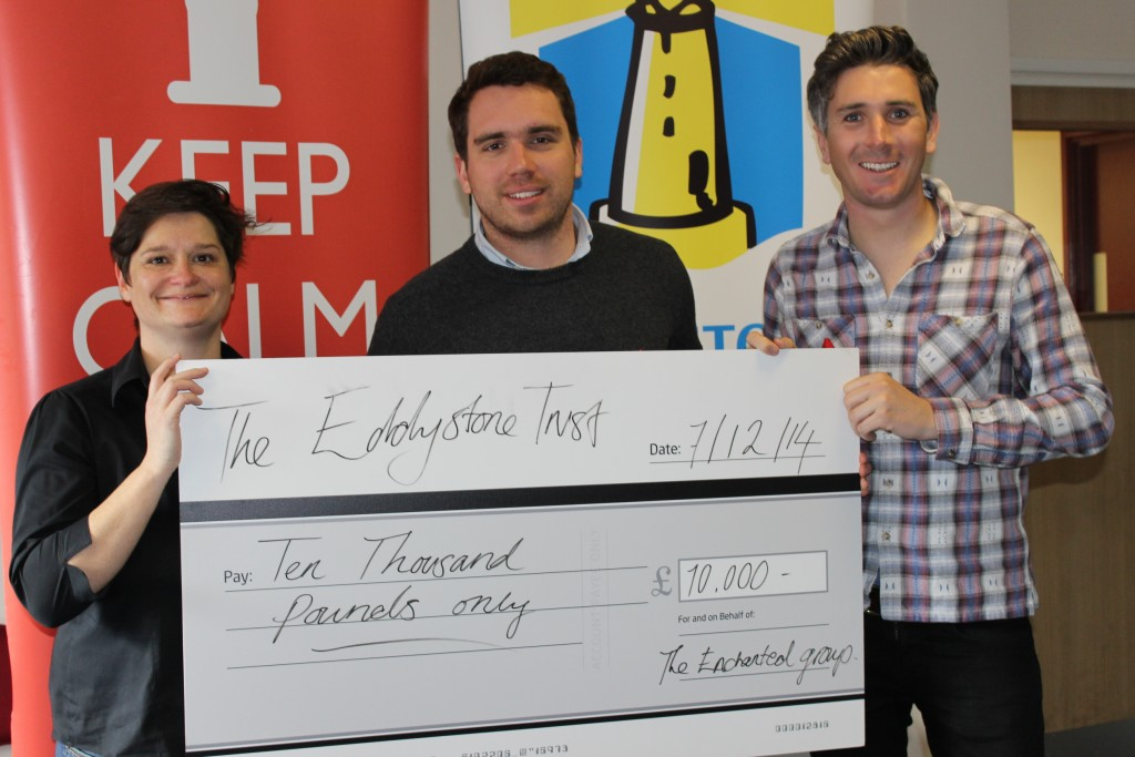 Sarah Aston from the Eddystone Trust receives a cheque for £10,000 from Tom Wye and Sam King of The Enchanted Group