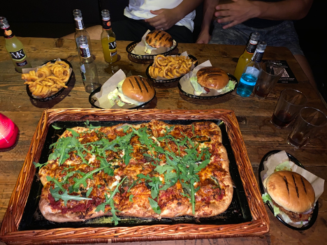 A selection of food at Timepiece. Includes burgers and a pizza