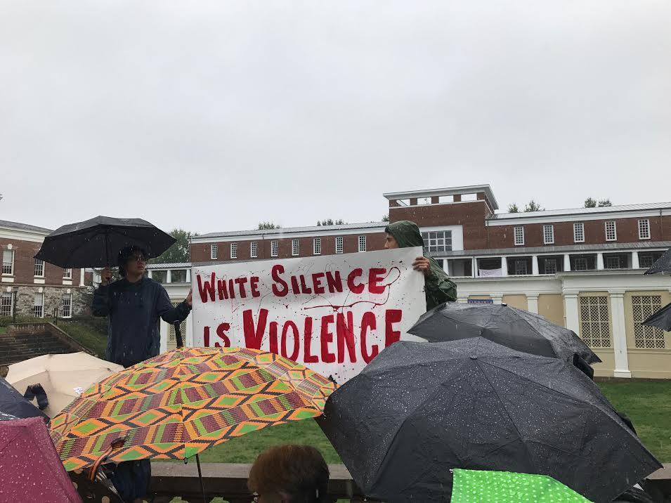 "Protesters hold signs that read ""white silence is violence"""