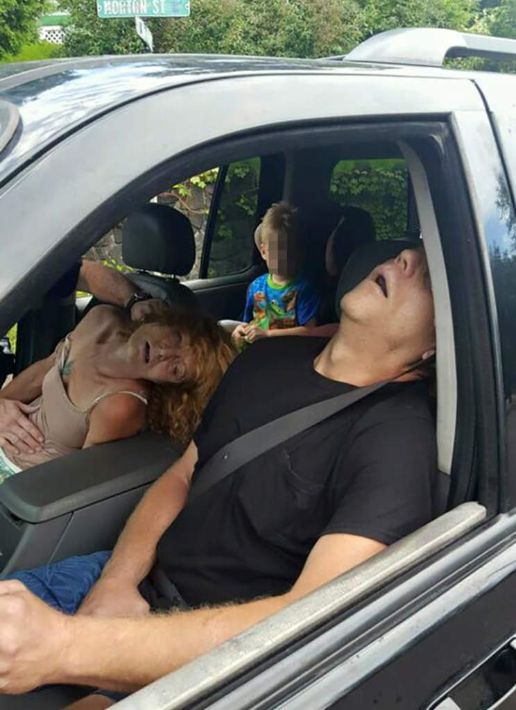 PA police released these harrowing images of two adults overdosing on heroin in a car with their child in the backseat