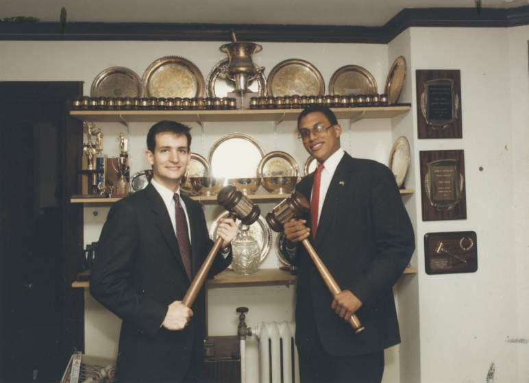 Ted Cruz (L) and David Panton (R) '92 who was Ted Cruz' debate teammate and close friend. Panton was also the Undergraduate Student Government president at the time of the photograph. June 5th, 1992.   The photograph might have been taken to celebrate their selection to the top debate team of the year by the American Parliamentary Debate Association (APDA) but no solid evidence to support this. According to the Whig-Cliosophic Society's 1992 Style Report, they received the award on April 22, 1992 at the ADPA  nationals. Cruz was also selected as the First Speaker of the Year and Panton was selected as the Second Speaker.  An article in the Daily Princetonian on April 8, 1992 confirms their selection for the team award and supports the possibility that this photo was taken for that purpose.   The three awards are on the right are Whig-Clio awards given to the pair.  The location of the photograph is uncertain but likely to be in the Whig-Clio office.