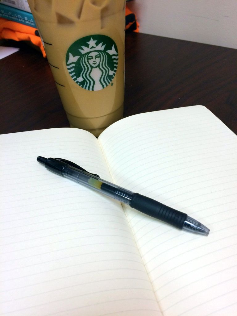 A photo of a starbucks iced coffee and an open moleskine notebook with a pen laying on top of it