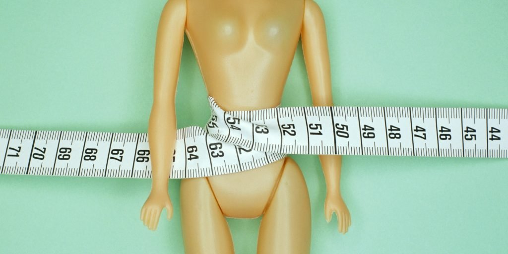 Female doll with tape measure around waist, portrait