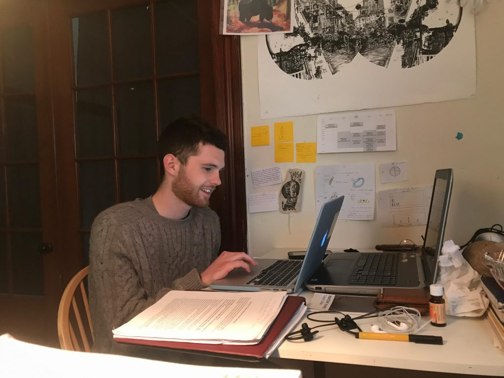 alternative studying Student sitting at a desk with two laptops in front of him