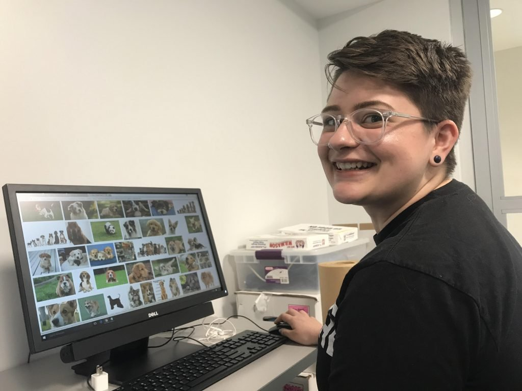 alternative studying Student in front of computer screen covered with pictures of puppies turns to smile at camera