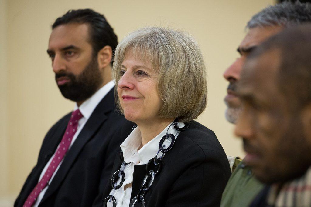 Theresa May sits between three men