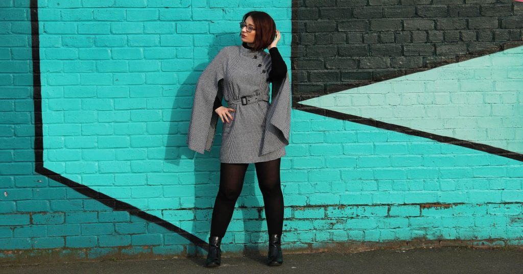 Image may contain: Long Sleeve, Wall, Overcoat, Coat, Footwear, Shoe, Brick, Sleeve, Person, Human, Apparel, Clothing