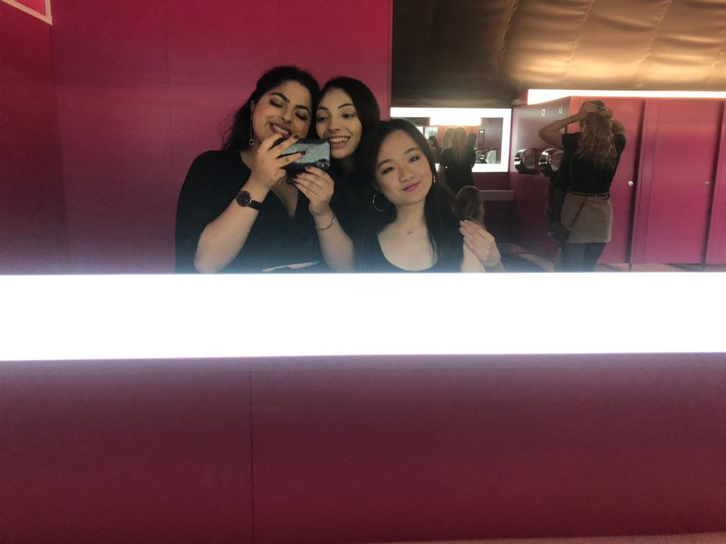 Three girls taking a picture in the mirror