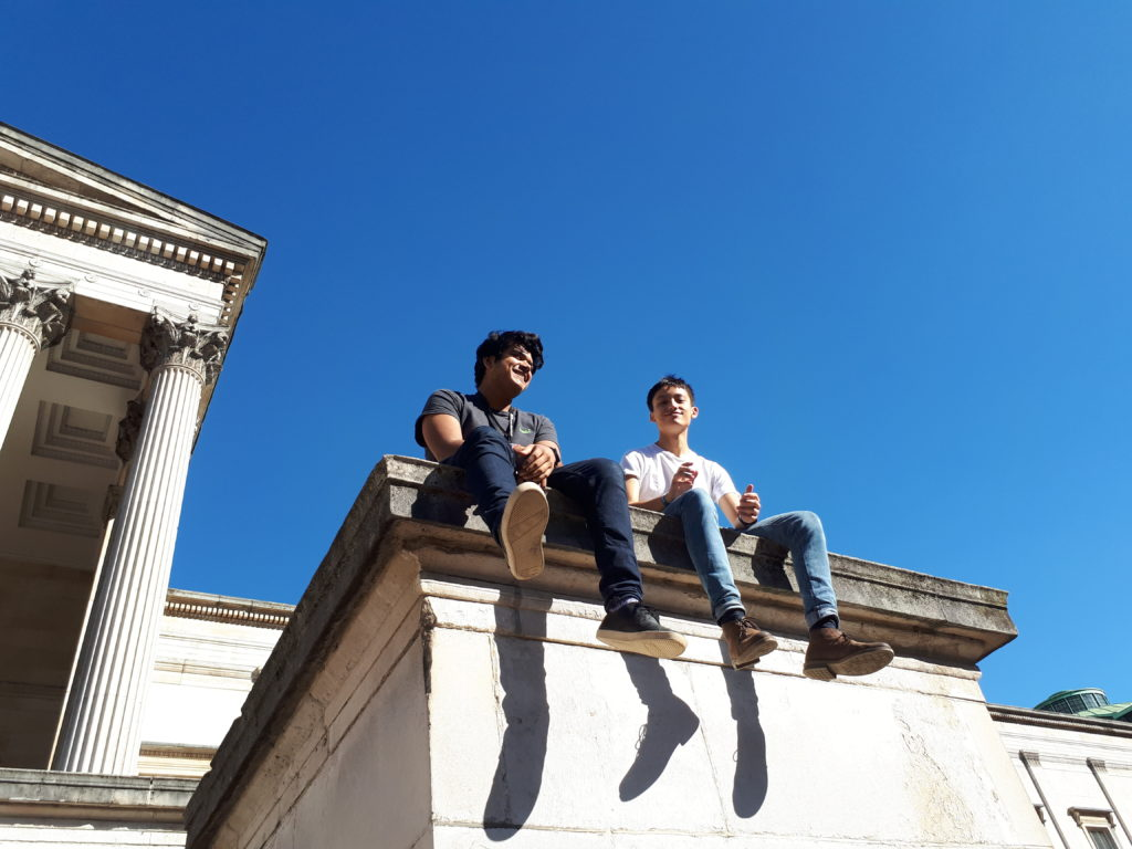 Two students sitting in UCL's main campus