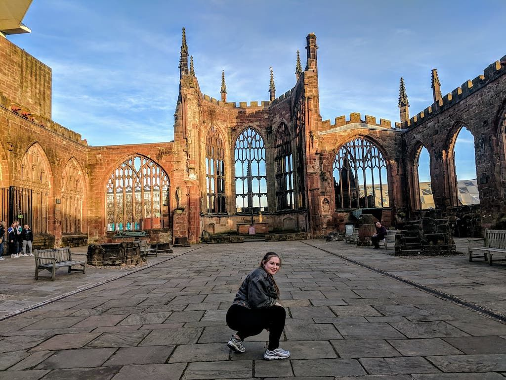 Image may contain: Cathedral, Church, Tower, Spire, Steeple, Downtown, Urban, City, Town, Furniture, Bench, Apparel, Shoe, Clothing, Footwear, Path, Walkway, Building, Architecture, Flagstone, Person, Human
