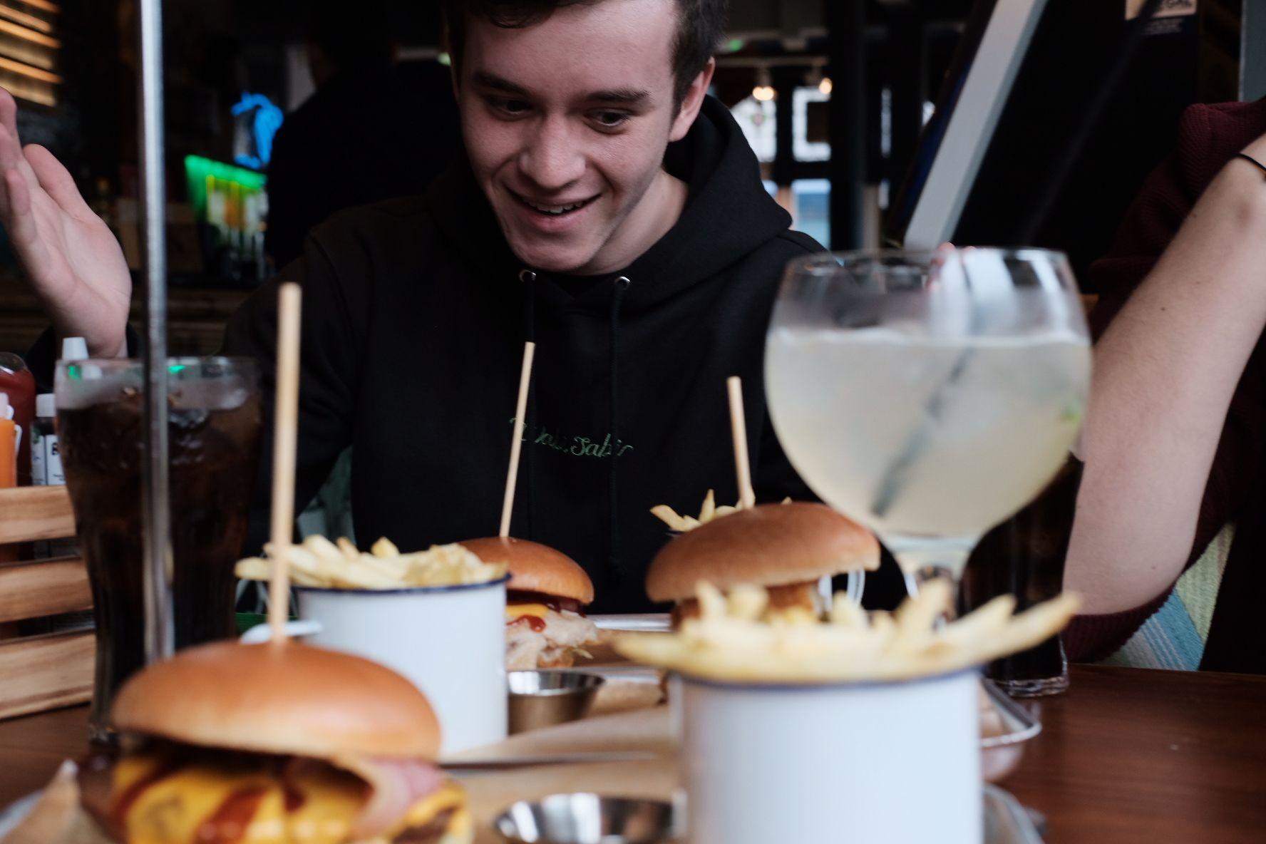 Image may contain: Restaurant, Person, Human, Food, Burger