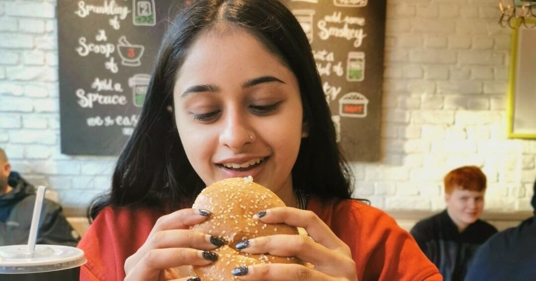 Image may contain: Female, Burger, Eating, Food, Person, Human