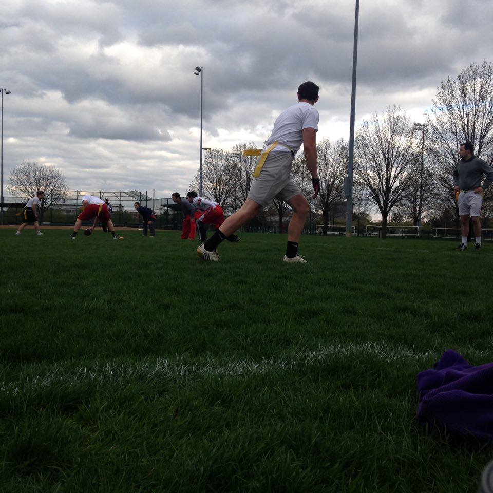 A man is preparing for the snap in a game of flag football