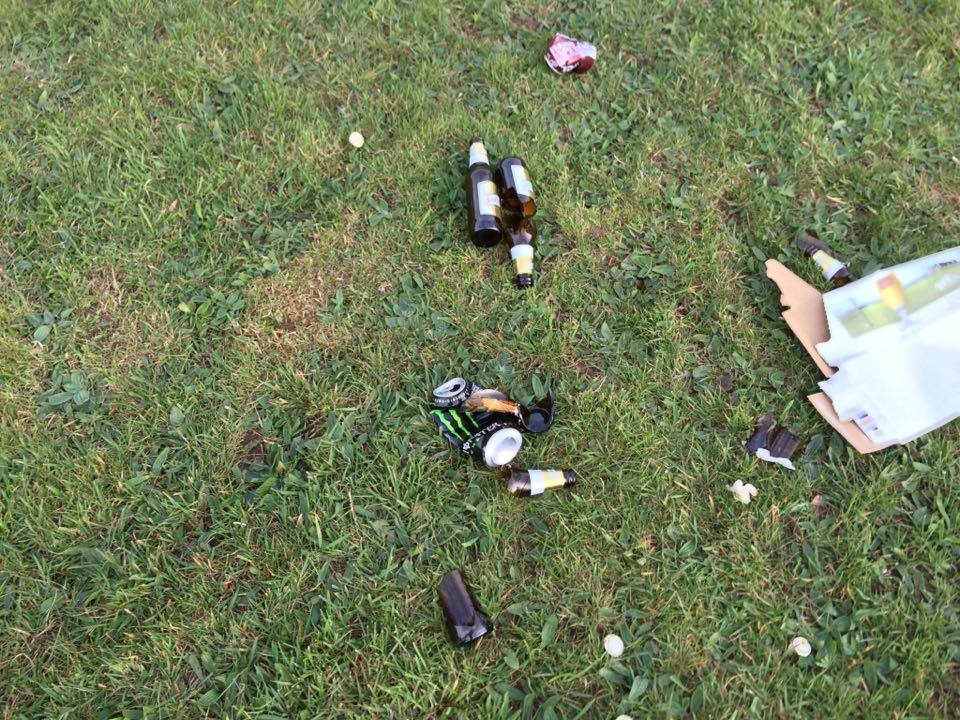 There are empty beer bottles strewn across the whole park