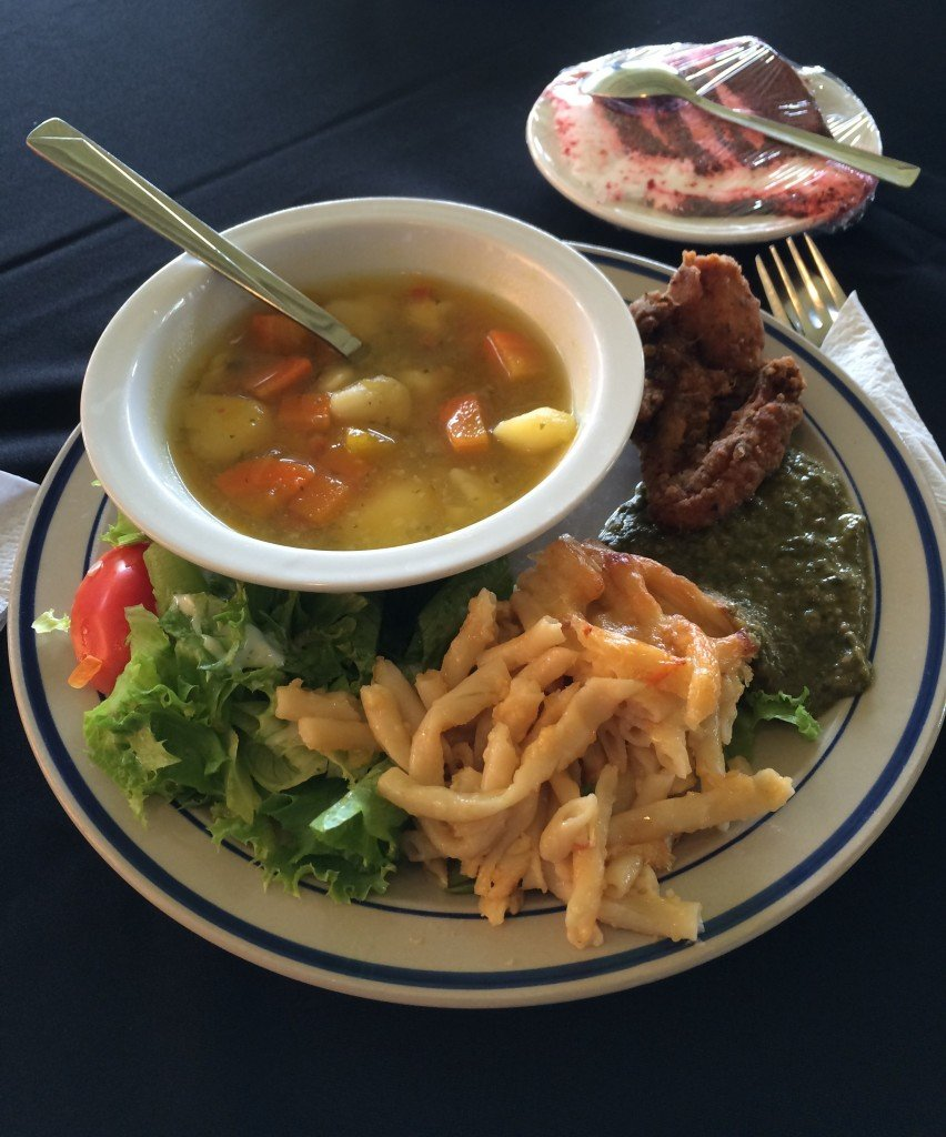 A plate of some popular Trini dishes: hearty soup, macaroni pie and callaloo - a mushy blend of green vegetables