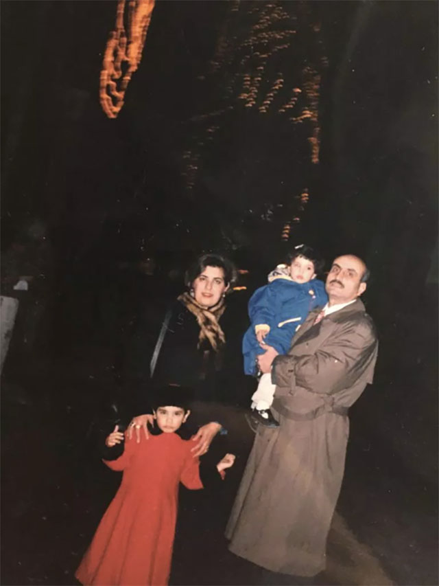 The family poses in front of a giant Christmas tree in Damascus, Syria in 2001