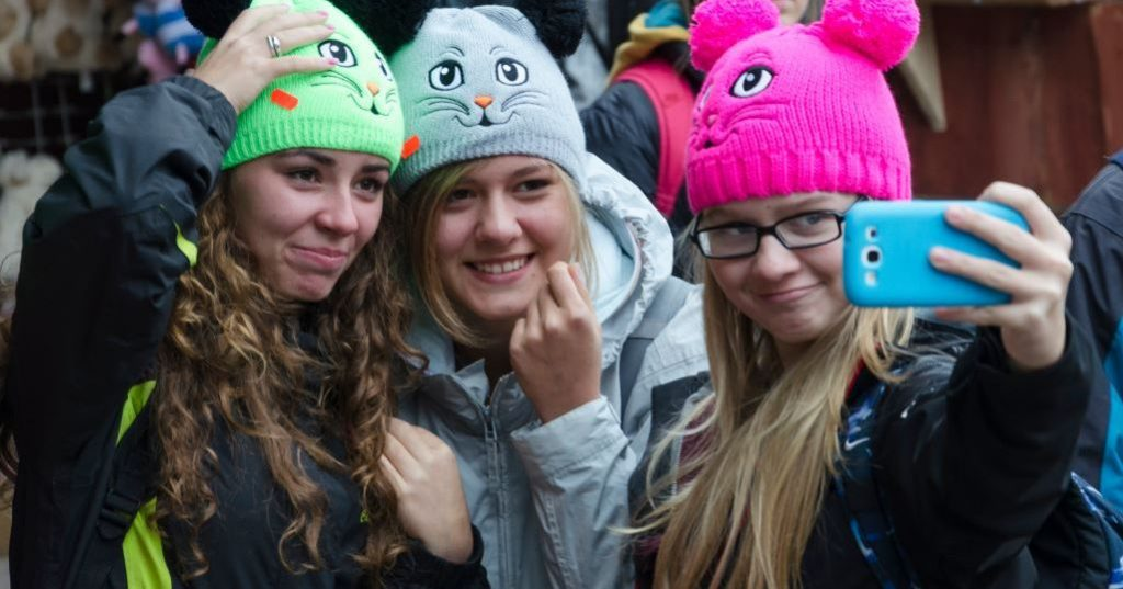 Image may contain: Crowd, Smile, Portrait, Face, Hat, Cap, Beanie, Human, Person, People