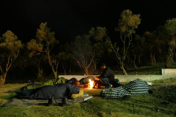 Sleeping around a fire under donated blankets to keep warm.