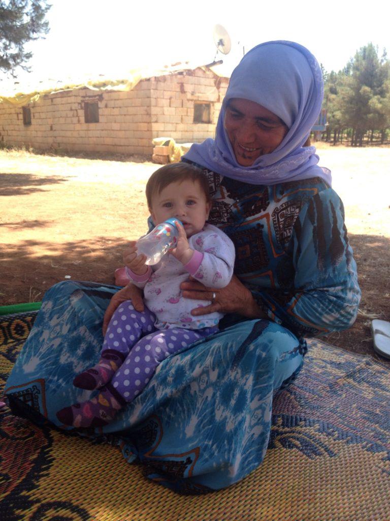 A Kurdish Syrian woman with her grandchild.