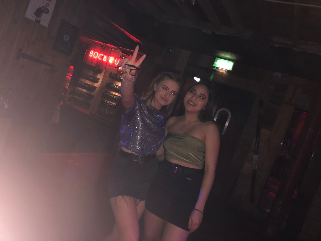 Image may contain: Woman, Bar Counter, Pub, Face, Night Life, Night Club, Skirt, Club, Female, Apparel, Clothing, Person, Human