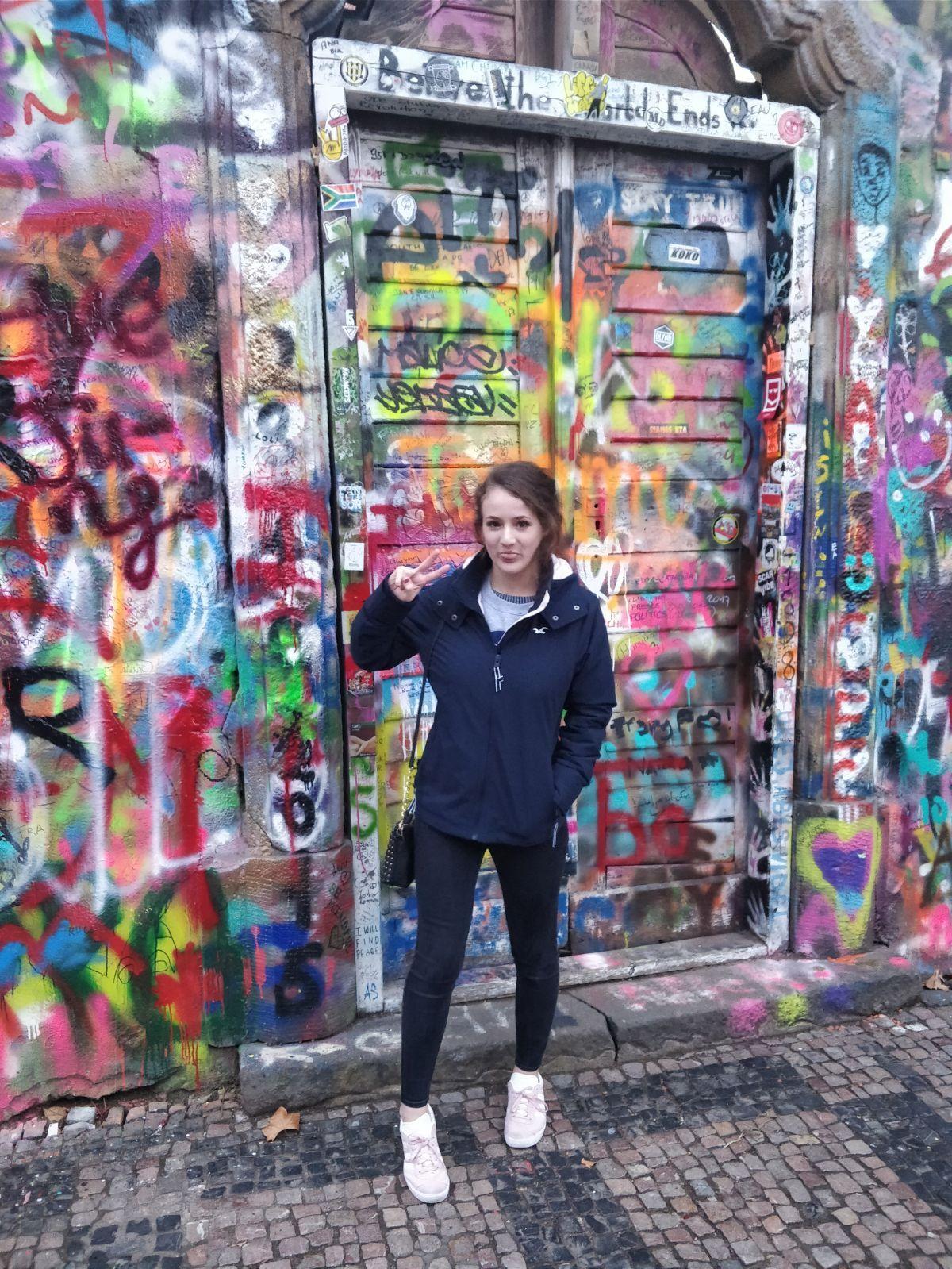 Image may contain: Overcoat, Coat, Female, Path, Walkway, Pants, Wall, Painting, Art, Mural, Graffiti, Human, Person, Footwear, Apparel, Shoe, Clothing