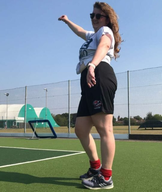 Lara posing with right arm up on a hockey astroturf in the sunshine