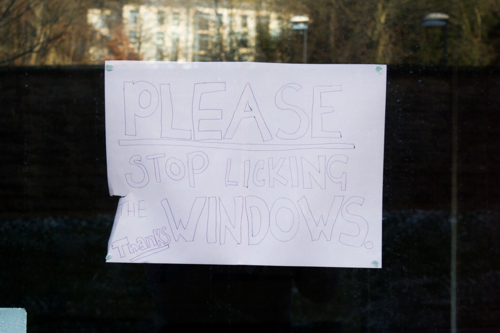 An A4 sign reads: 'PLEASE STOP LICKING THE WINDOWS'.