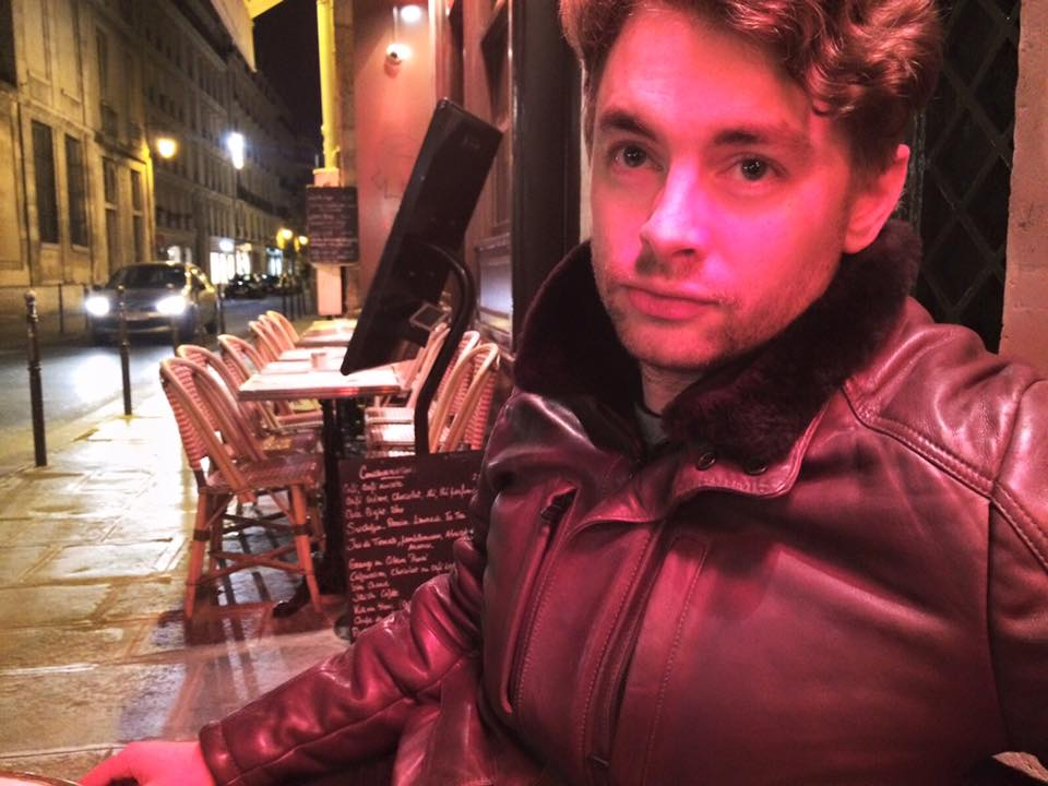 At night on a European Street, Paul Joseph Watson sits outside a restaurant. A red light is cast onto his face by the nearby signage