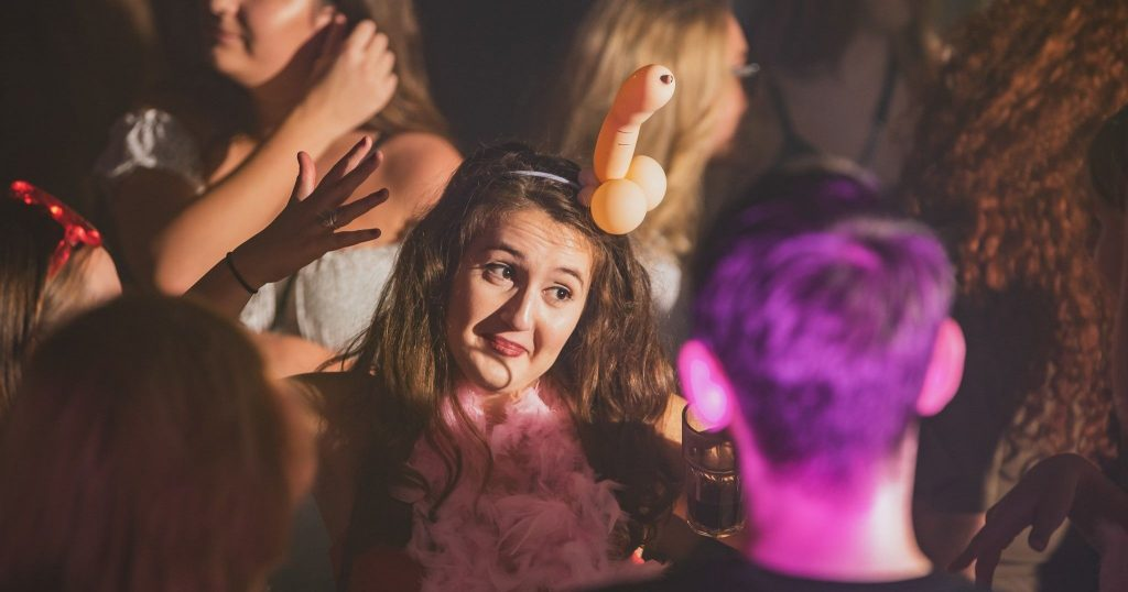Image may contain: Night Life, Feather Boa, Scarf, Night Club, Club, Clothing, Apparel, Human, Person