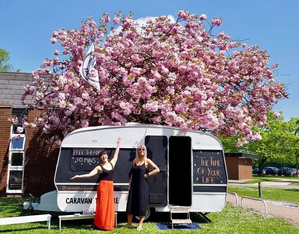 Image may contain: Female, Outdoors, Caravan, Dress, Clothing, Apparel, Van, Transportation, Vehicle, Grass, Flower, Blossom, Vegetation, Bush, Person, Human, Plant