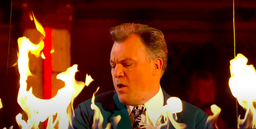 Balls playing a piano with flames behind him