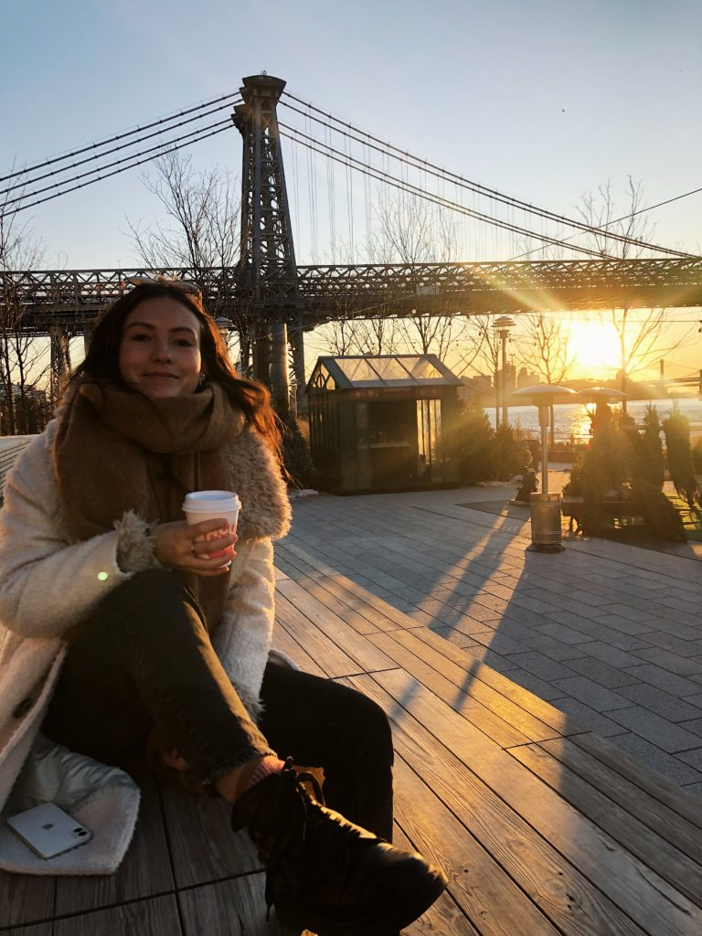 Emma Bates is sat down on what looks like a wooden pier, with a hot drink, wearing a bit winter coat and scarf as the sun sets over a bridge behind her.