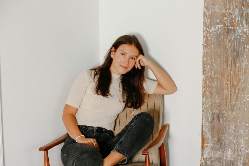 Emma Bates sat in a tartan chair, with legs crossed and her head casually resting on her hand. She wears black stonewashed jeans and a plain cream t-shirt.