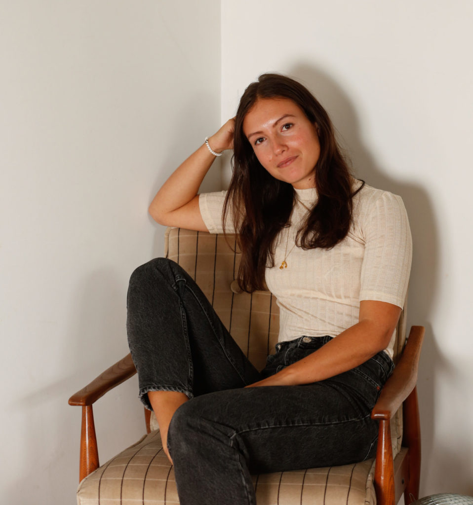 Emma Bates sits in a tartan chair, with legs crossed and her head casually resting on her hand. She wears black stonewashed jeans and a ribbed cream t-shirt.