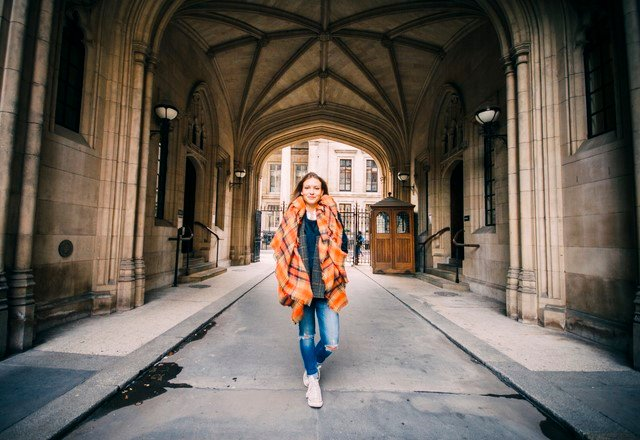 Full-body walking shot of a younger Emma Bates walking through a neo-gothic stone archway.