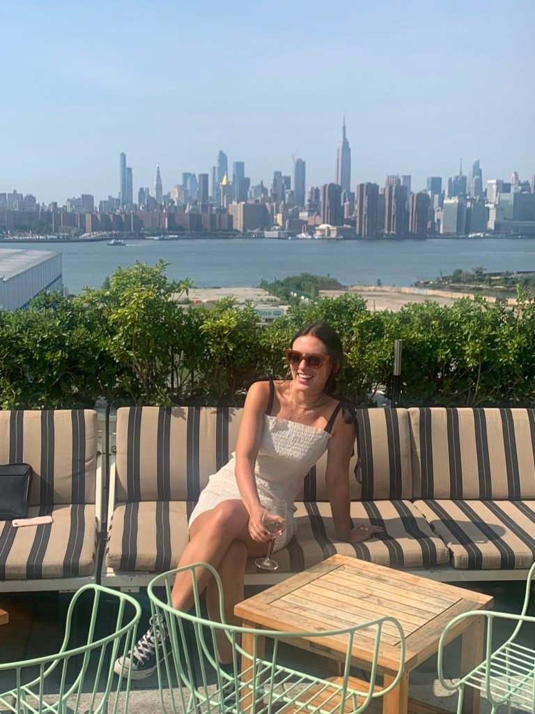 Emma Bates sits on the lounge bench of a sunny rooftop bar, wearing a white dress, retro sunglasses, and laughing as she looks off-camera. Behind her is the New York skyline.