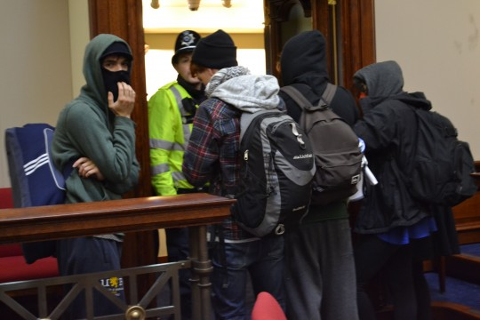 Occupiers cover their faces from the bitter cold of the senate chamber.