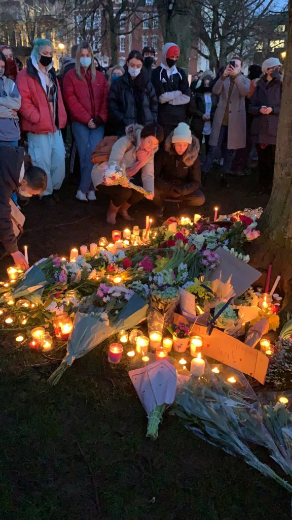 crowds gathered for a vigil for Sarah Everard on college green with flowers and candles