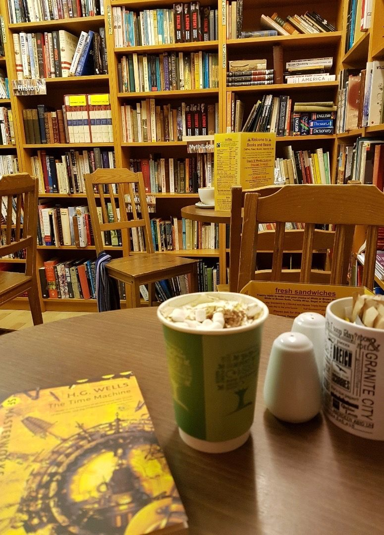 Image may contain: Coffee Cup, Cup, Library, Bookstore, Shop, Book, Chair, Bookcase, Shelf, Room, Indoors, Furniture