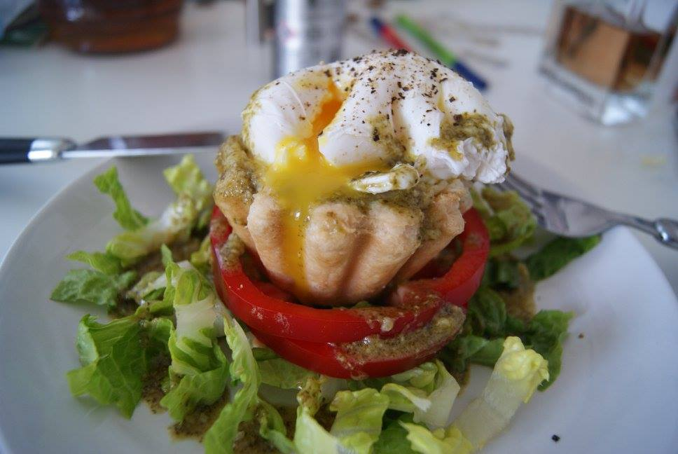 Poached egg on mashed potato filled pastry cup resting on a bed of salad with honey and mustard dressing and black pepper.