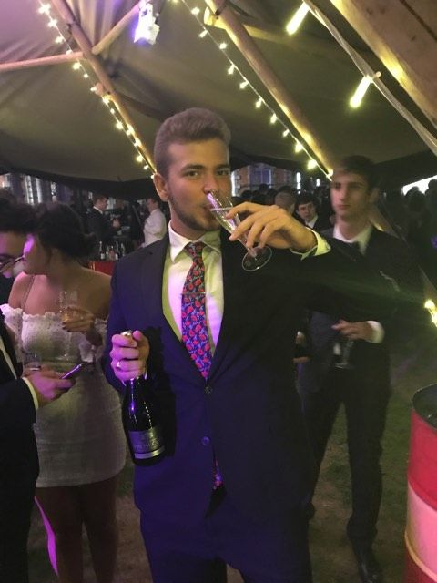 Image may contain: Drinking, Dress, Alcohol, Tuxedo, Party, Night Life, Beverage, Drink, Jacket, Blazer, Suit, Overcoat, Coat, Person, Human, Apparel, Clothing, Accessory, Accessories, Tie