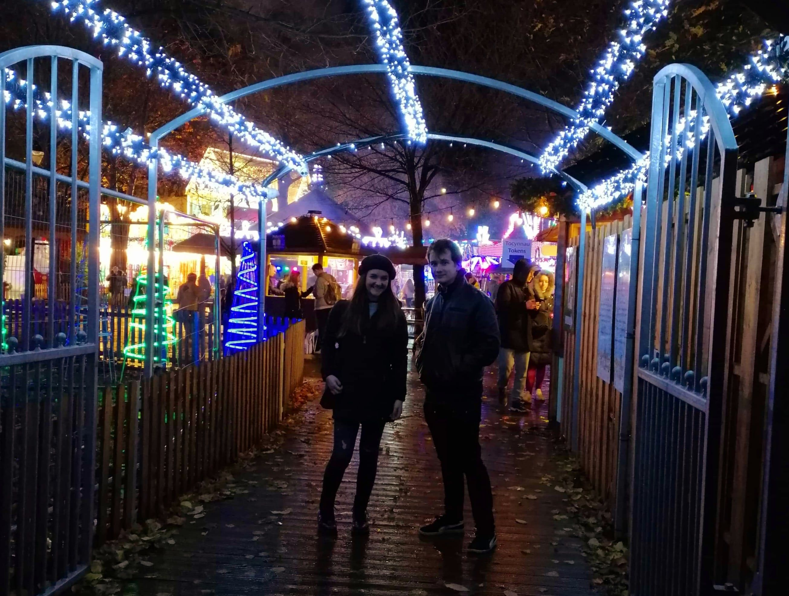 Image may contain: Overcoat, Coat, Lighting, Apparel, Footwear, Clothing, Shoe, Amusement Park, Theme Park, Sidewalk, Pavement, Path, Person, Human