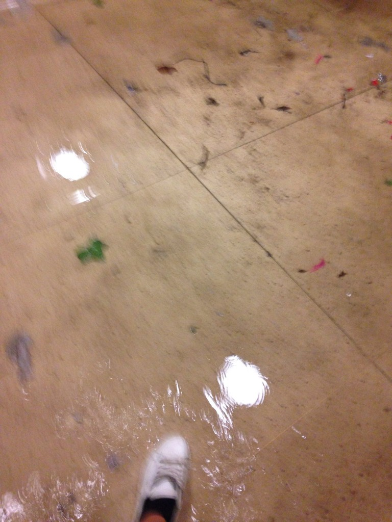 The floor in the bathroom besmirched by various things.