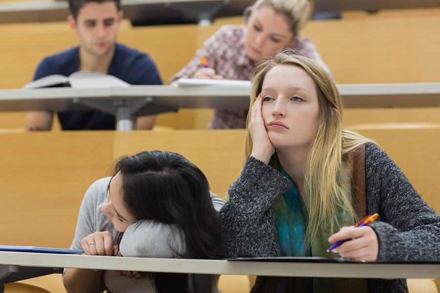 Demotivated students sitting in a lecture hall with one girl nap