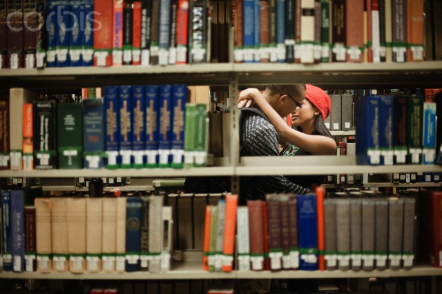 Couple kissing in library --- Image by © Troy House/Corbis