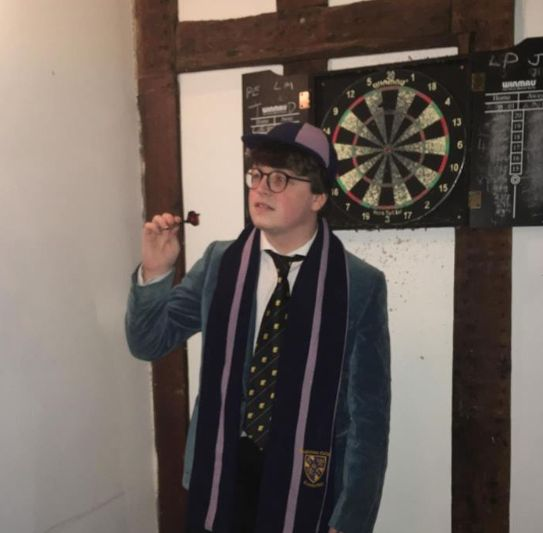 Image may contain: Game, Darts, Suit, Overcoat, Coat, Apparel, Clothing, Human, Person, Accessories, Accessory, Tie