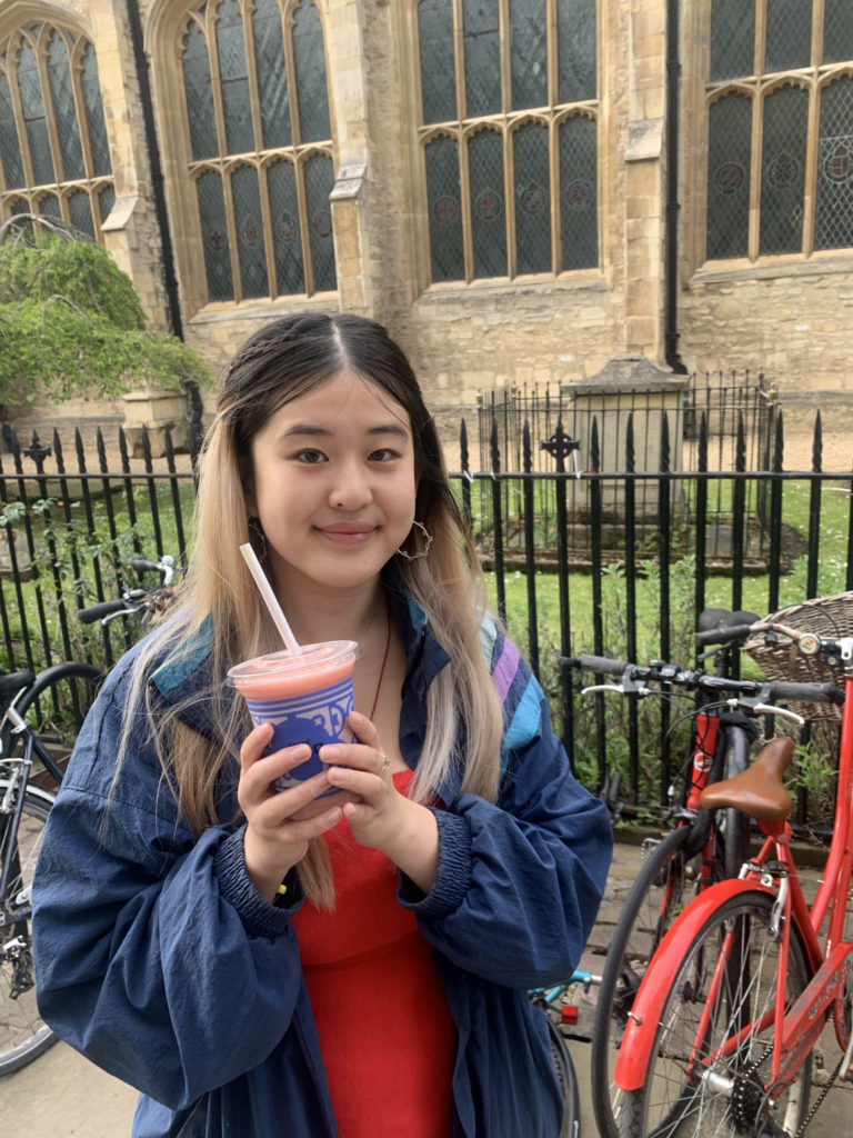Girl holding a Caffè Nero fruit booster and smiling