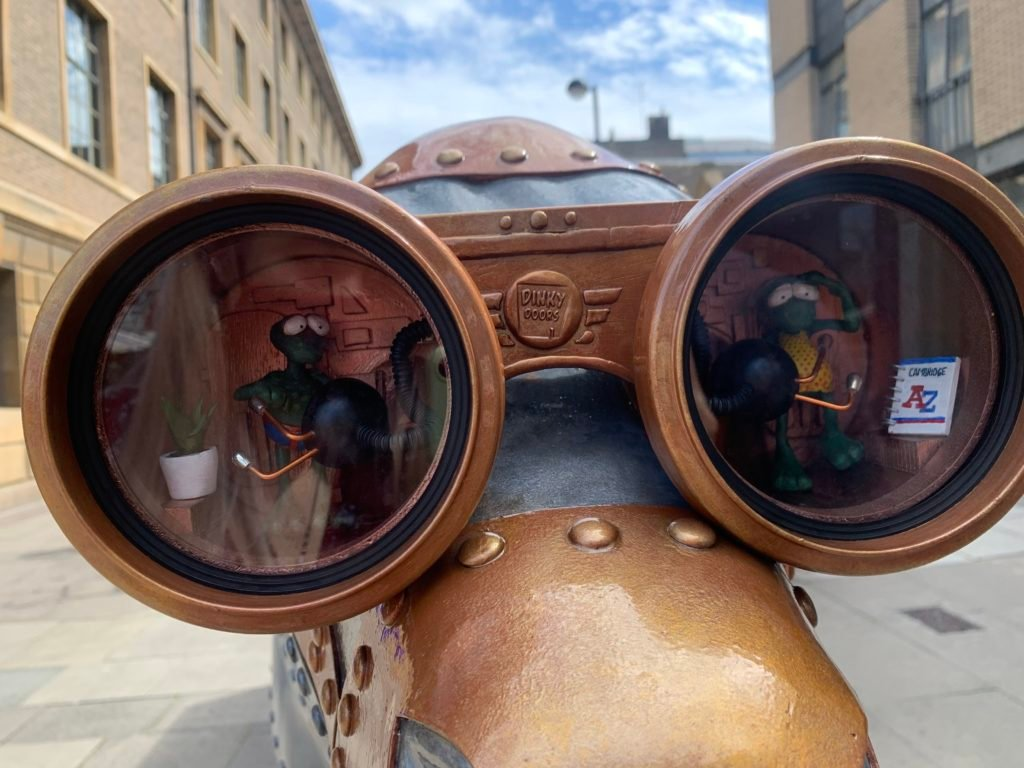 Close up of a mechanical cow depicting two small aliens in the goggles