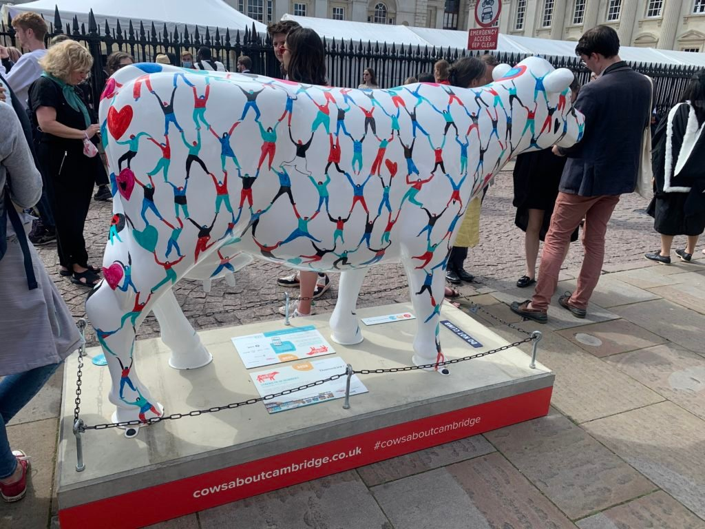 White cow with many stick figures holding hands painted on it