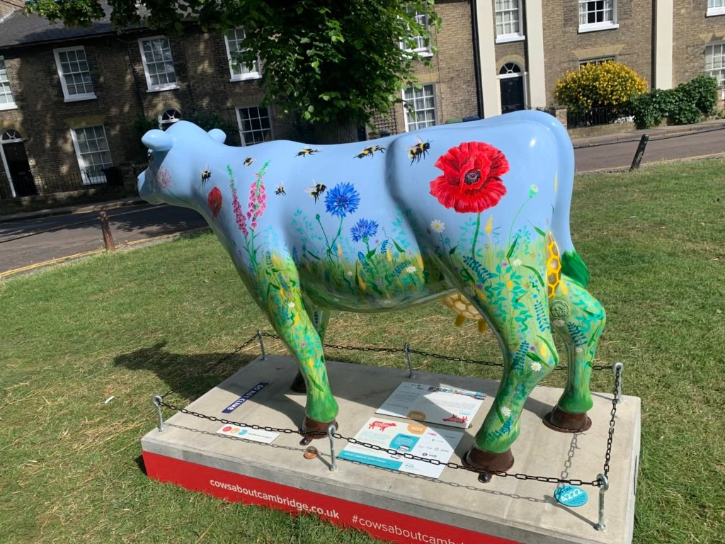 Blue cow statue with flowers painted onto it